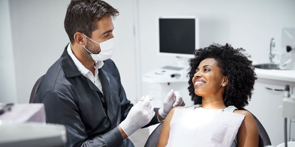 dentist examining smiling female patient in clinic